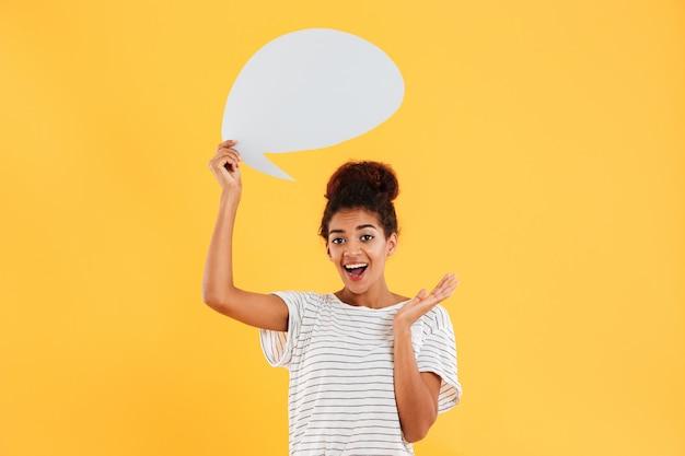 Joven africana pensativa feliz dama y sosteniendo el bocadillo en blanco aislado sobre amarillo