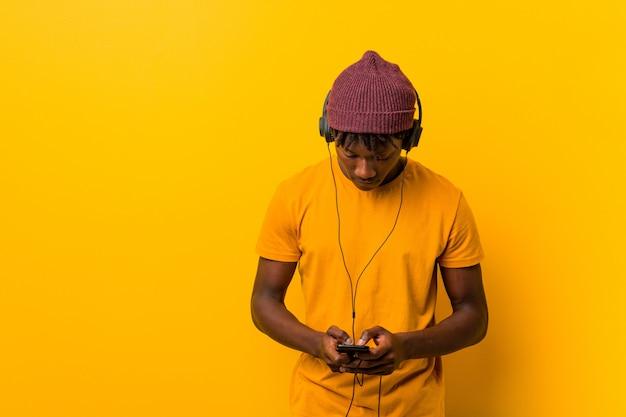 Joven africana de pie contra una pared amarilla con un sombrero escuchando música con un teléfono