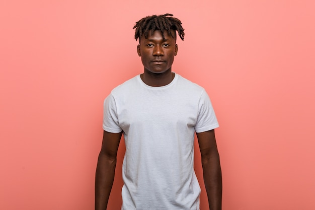 Joven africana de pie contra la pared rosa