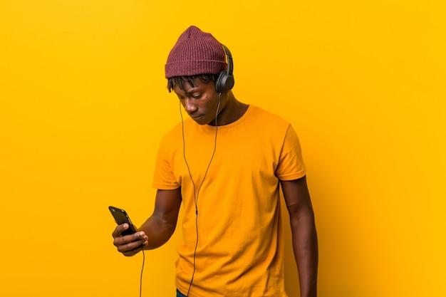Joven africana de pie sobre un fondo amarillo con un sombrero escuchando música con un teléfono