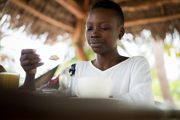 Joven africana en el resort desayunando