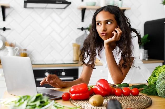 Joven africana tiene mirada pensativa escribiendo algo en una computadora portátil en un escritorio de cocina con verduras