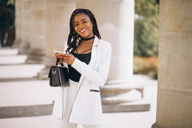 Joven africana en traje blanco con teléfono