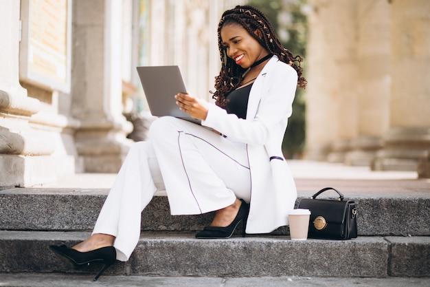 Joven africana vestida de blanco usando laptop