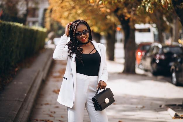 Joven africana vestida con traje blanco fuera de la calle