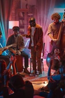 Joven africano cantando mientras su banda toca instrumentos durante la actuación en el club