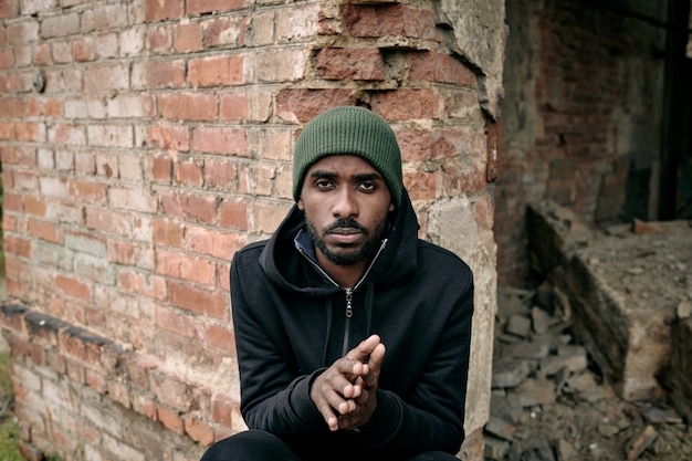Joven africano con capucha y gorra sentado junto a la pared de ladrillo