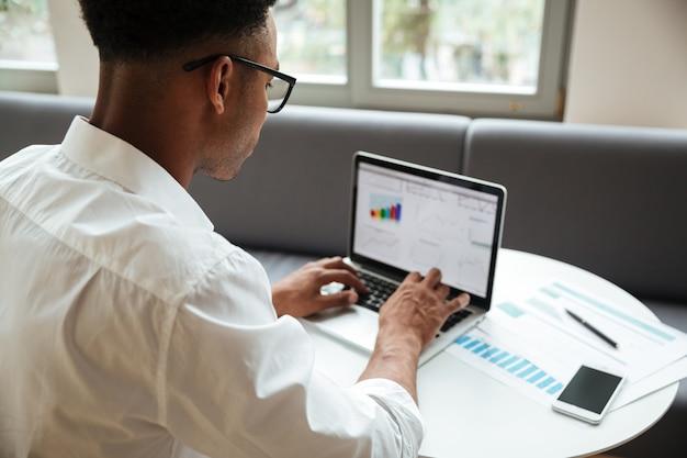 Joven africano concentrado sentado coworking