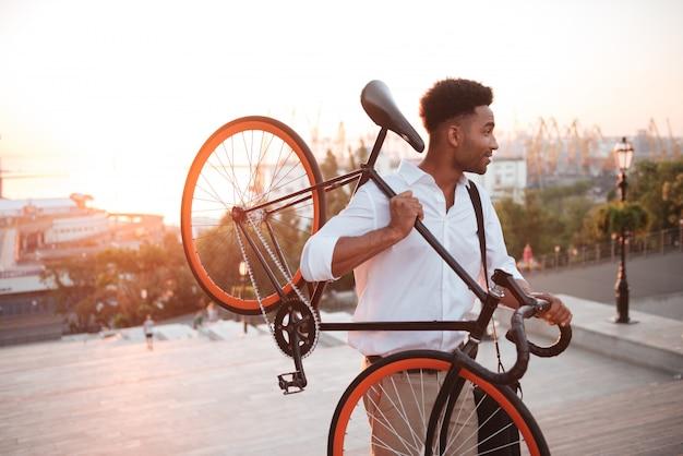 Joven africano concentrado temprano en la mañana con bicicleta