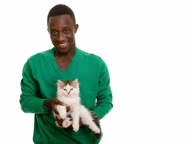 Joven africano feliz sonriendo y sosteniendo lindo gato