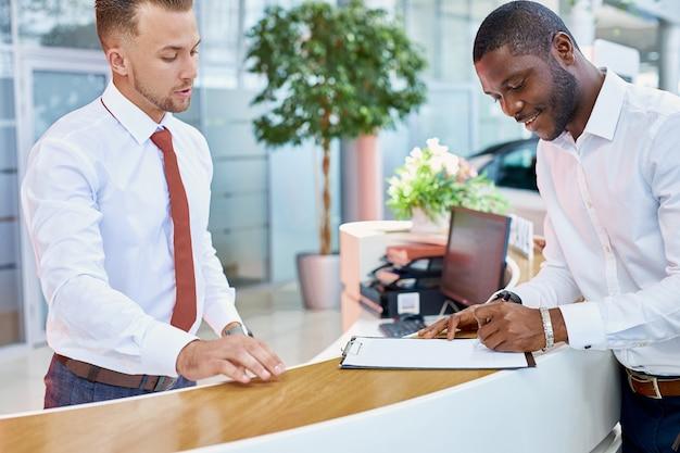 Joven africano firma un contrato en la tienda del concesionario