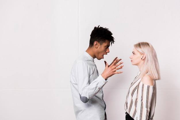 Un joven africano gritando a su novia contra la pared blanca