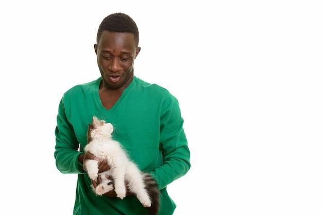 Joven africano haciendo cara divertida mientras sostiene lindo gato