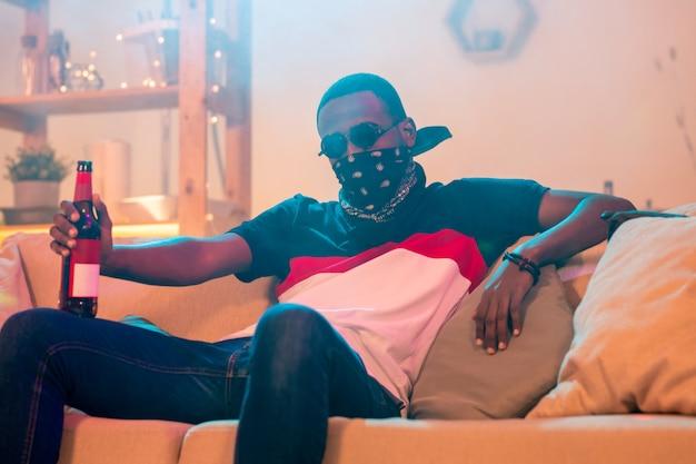 Joven africano en pañuelo negro en la cara, jeans y camiseta con una botella de cerveza mientras se relaja en un sofá suave en casa