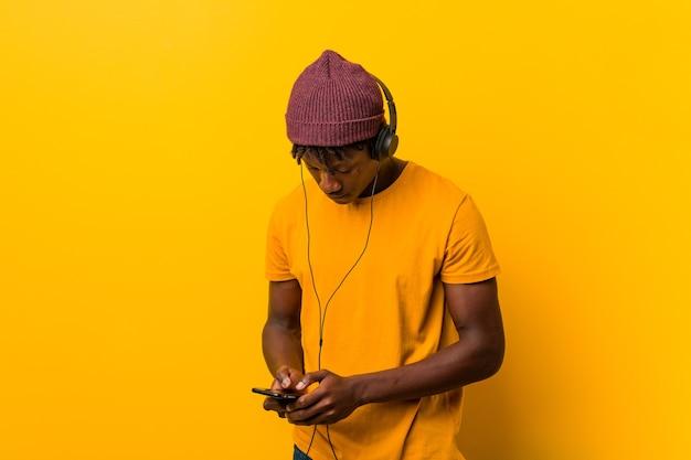 Joven africano de pie contra una pared amarilla con sombrero escuchando música con un teléfono