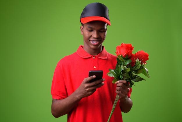 Joven africano con ramo de rosas contra la pared verde