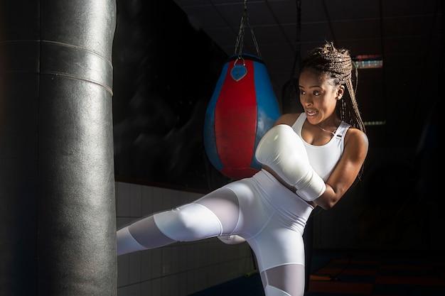 Joven afro entrenando kickboxing dentro del gimnasio, fuerza, inspiración, determinación.