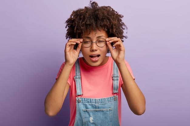 Joven afro mantiene las manos en el marco de las gafas, intenta concentrarse