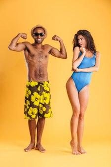 Joven afro mostrando bíceps a su novia aislado en la pared naranja
