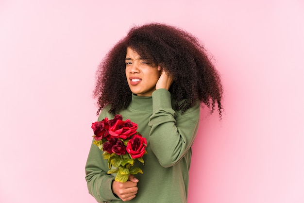Joven afro mujer sosteniendo una rosas aisladas joven afro mujer sosteniendo una rosas cubre orejas con las manos.