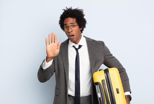 Joven afro negro que parece serio, severo, disgustado y enojado mostrando la palma abierta haciendo gesto de parada