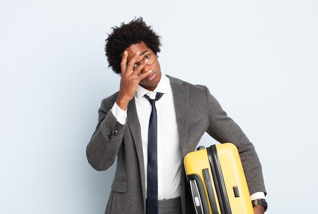 Joven afro negro que se siente aburrido, frustrado y con sueño después de una tarea tediosa, aburrida y tediosa, sosteniendo la cara con la mano