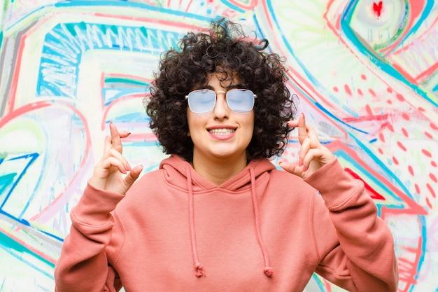 Joven afro sonriendo y cruzando ansiosamente ambos dedos, sintiéndose preocupada y deseando o esperando buena suerte en la pared de graffiti