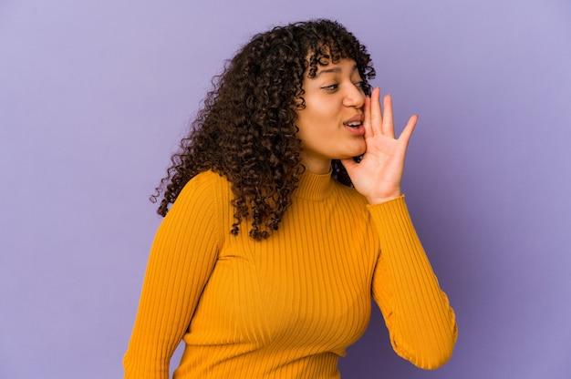 Joven afroamericana afro aislada está diciendo una noticia secreta de frenado en caliente y mirando a un lado