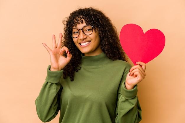 Joven afroamericana afro sosteniendo un corazón de san valentín alegre y confiado mostrando gesto ok.