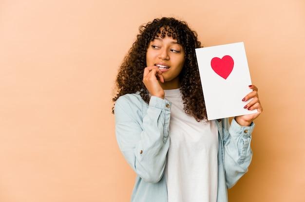 Joven afroamericana afro sosteniendo una tarjeta del día de san valentín relajado pensando en algo mirando un espacio de copia.