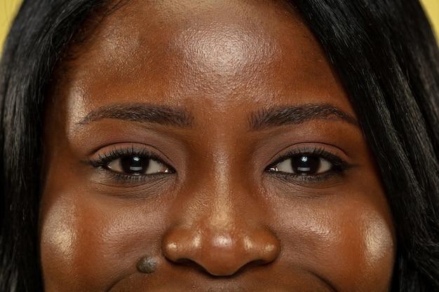 Joven afroamericana aislada en espacio amarillo, expresión facial. ojos de mujer hermosa cerca retrato