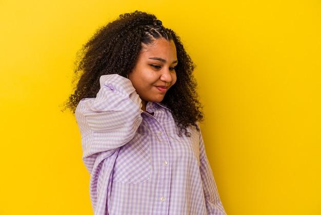 Joven afroamericana aislada en la pared amarilla con dolor de cuello debido al estrés, masajeando y tocándolo con la mano.