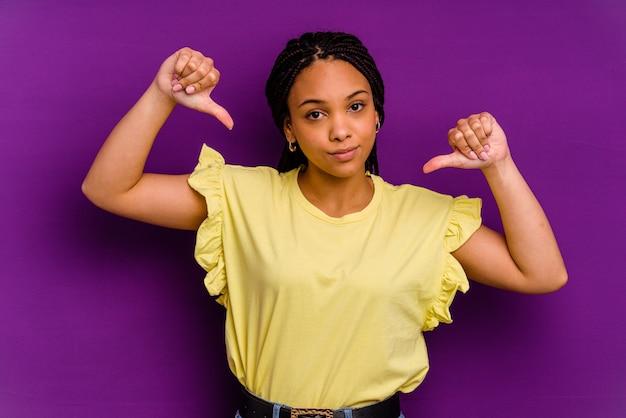Joven afroamericana aislada en la pared amarilla joven afroamericana aislada en la pared amarilla se siente orgullosa y segura de sí misma, ejemplo a seguir.