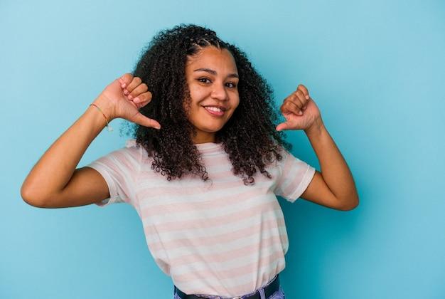 Joven afroamericana aislada en la pared azul se siente orgullosa y segura de sí misma, ejemplo a seguir.