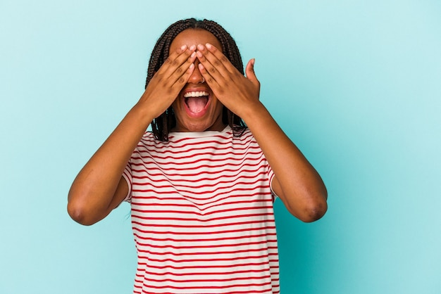 Joven afroamericana aislada sobre fondo azul cubre los ojos con las manos, sonríe ampliamente esperando una sorpresa.