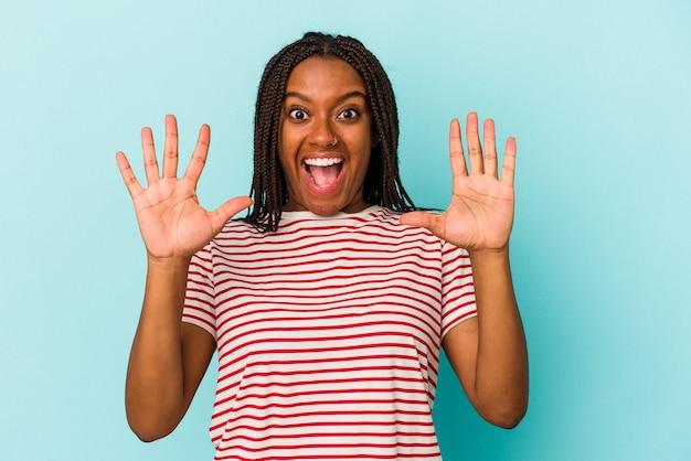 Joven afroamericana aislada sobre fondo azul recibiendo una agradable sorpresa, emocionada y levantando las manos.