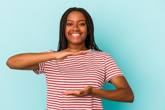 Joven afroamericana aislada sobre fondo azul sosteniendo algo con ambas manos, presentación del producto.