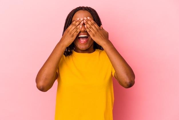 Joven afroamericana aislada sobre fondo rosa cubre los ojos con las manos, sonríe ampliamente esperando una sorpresa.
