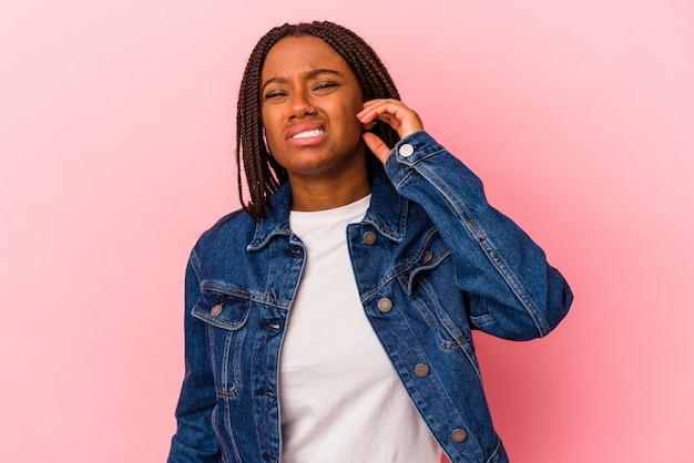 Joven afroamericana aislada sobre fondo rosa cubriendo las orejas con los dedos, estresada y desesperada por un ambiente ruidoso.