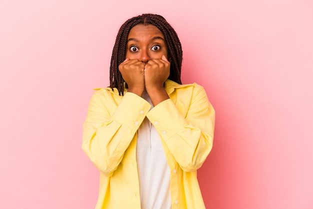 Joven afroamericana aislada sobre fondo rosa mordiéndose las uñas, nerviosa y muy ansiosa.