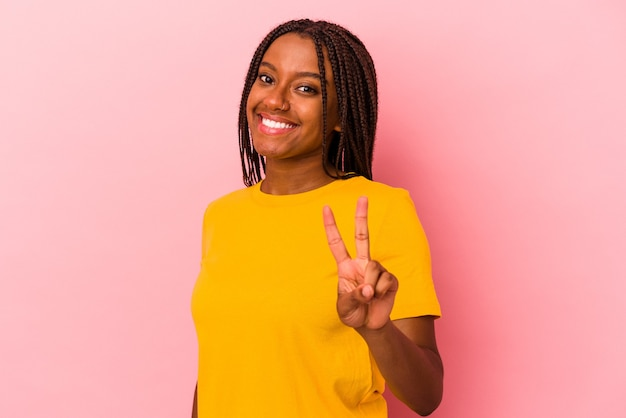 Joven afroamericana aislada sobre fondo rosa mostrando el signo de la victoria y sonriendo ampliamente.