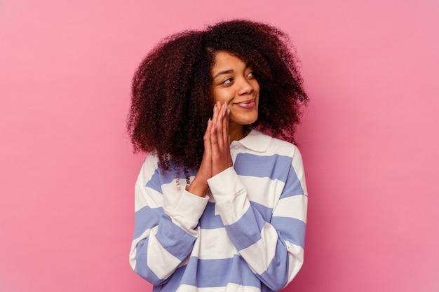 Joven afroamericana aislada sobre fondo rosa rezando, mostrando devoción, persona religiosa en busca de inspiración divina.