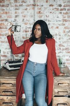 Joven afroamericana en bata roja en fondo urbano sostiene el teléfono en tus manos y hace fotos
