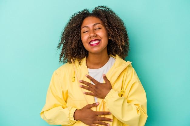 Joven afroamericana con cabello rizado aislado sobre fondo azul se ríe felizmente y se divierte manteniendo las manos en el estómago.