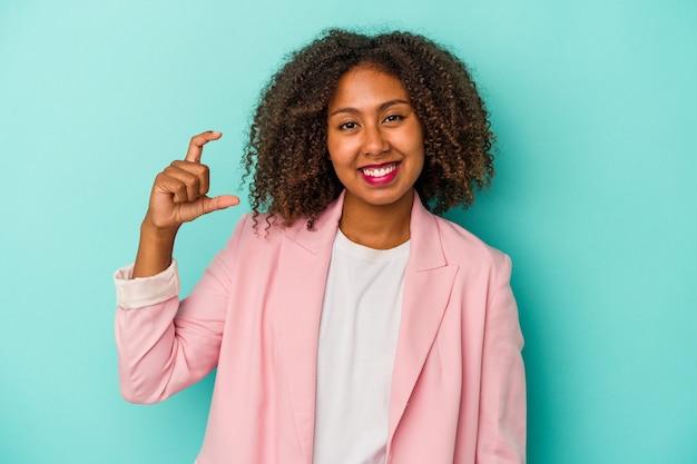 Joven afroamericana con cabello rizado aislado sobre fondo azul sosteniendo algo pequeño con los dedos índices, sonriente y confiado.