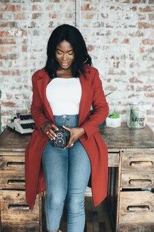 Joven afroamericana en capa roja en fondo urbano tiene la cámara retro en sus manos