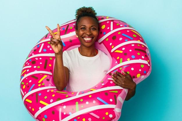 Joven afroamericana con donut inflable aislado sobre fondo azul que muestra el número dos con los dedos.