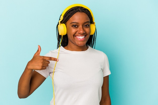 Joven afroamericana escuchando música aislada sobre fondo azul persona apuntando con la mano a un espacio de copia de camisa, orgulloso y seguro