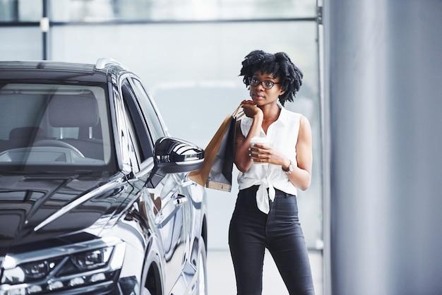 Joven afroamericana en gafas se encuentra en el salón del automóvil cerca del vehículo con el paquete en las manos.
