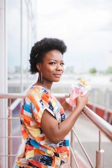 Joven afroamericana con hamburguesa en sus manos al aire libre